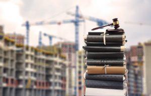 Gesetzestexte, Richterhammer vor Großbaustelle, symbolhaftes Bild zu Baurecht