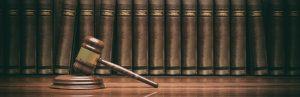 Hintergrundbild mit Justizsymbolik: Hammer, Gesetzestexte